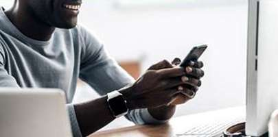 Image of a gentleman sat at a desk holding his mobile phone ready to tap out a text.